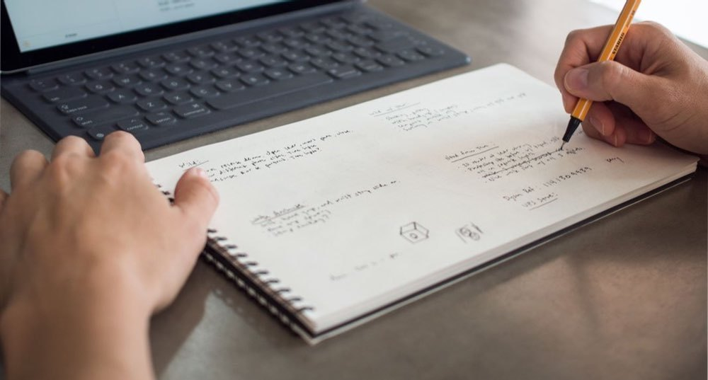 Photo: A hand holding a pencil sketches in the Panobook, a wide sketchbook with a light dot grid